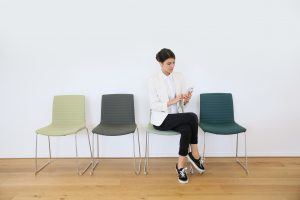 trendy girl in waiting room sending message with smartphone